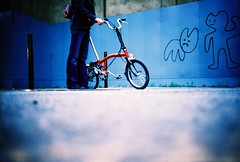 brompton & graffiti (lomokev) Tags: blue london bike sarah graffiti lomo lca xpro lomography crossprocessed xprocess girlfriend 100v10f lomolca cycle characters agfa jessops100asaslidefilm agfaprecisa fahrrad vlo pugh lomograph fiets brompton fiance bicicletta agfaprecisa100 cruzando spuw fianc mybird bicis evilbunny precisa pureevilbunny jessopsslidefilm rockcakes rockcake publishedinjpg submittedtojpg flickr:user=rockcake rota:type=showall rota:type=portraits rota:type=stilllife file:name=lomo1005a38