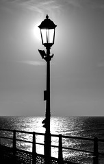 Sun Lamp (clive_metcalfe) Tags: lamp light sun pier eastbourne ocean sea sky water uk sol post blackwhite mono illumiation