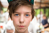 young boy with basecap looking into the camera, blurred people in background (Armin Staudt) Tags: blue boy portrait people white macro cute male beautiful beauty hat childhood closeup hair cub clothing cool model eyes european child background innocent young son human cap nicolas flimsy poise nonchalant baseballcap gracile doup