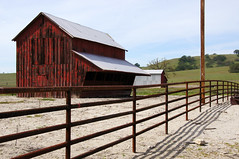 Along A Country Road (nedlugr) Tags: california ca usa fence redbarn barn shadows rust ruralwest rural rustic lines corrugated tinroof feedingbarn montereycounty omot