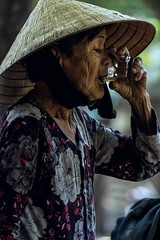 Thirsty work. (Odkaella) Tags: old travel portrait people woman hot colour travelling canon outdoors eos focus soft shadows zoom tea drink bokeh icedtea wanderlust depthoffield sweaty vietnam hoian elderly observe tropical daytime local streetfood thirsty humid gulp parched freebies hydrate nonla 60d
