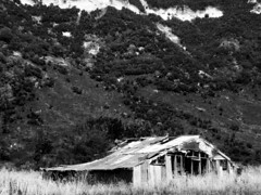 Abandoned House under the Cliffs (Vaughan K Bourke) Tags: blackandwhitephoto blackandwhite nature landscape barn cliff hills abandoned run down wooden iron grass newzealand vaughan bourke
