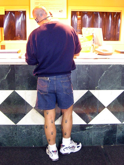 Man with animal track tattoos up and down his legs and the back of his head.