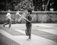 Final Systems Check in Progress... (Dinozauw) Tags: street streetphotography boy child children paperplane tamanbungkul bungkulpark bw blackandwhite monochrome surabaya indonesia asian southeastasia attractions local toys plane park leisure bokeh black white tamron14150mmf3558diiii people vignette candid joy expression kid outdoor urban emotions unposed