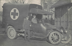 Two men pose beside a WWI ambulance