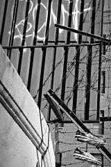 """Bent"" (Robert S. Photography) Tags: street bw sneakers hanging shoefiti wall building brooklyn newyork nikon monochrome coolpix l340 iso80 december 2016"