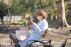 Young woman sitting on bench and watching screen on tablet (Apricot Cafe) Tags: img12587 20s asianethnicity canonef85mmf18usm japan japaneseethnicity tokyo afternoon bench charming cheerful digitaltablet enjoying forest oneperson onlywomen outdoors park people selectivefocus sitting sunray sunlight tranquility winter woman youngadult mitakashi tōkyōto jp