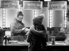 nocturnal market 02 (byronv2) Tags: edinburgh edinburghbynight edimbourg scotland blackandwhite blackwhite bw monochrome peoplewatching candid street night nuit nacht princesstreet princesstreetgardens market streetmarket festivemarket eat eating food sausage foodkiosk foodstall woman cooking diner streetfood burger venison venisonburger stall kiosk