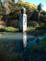 A Source (Sauce) of Mystery (Steve Taylor (Photography)) Tags: bottle sauce maori artwork monument rope art sculpture blue green brown concrete water avonriver river stream newzealand nz southisland canterbury christchurch cbd city bush tree reflection sunny sunshine