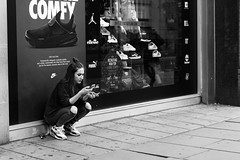 Not So Comfy (Cliff.j) Tags: knees outdoor smoking girl squatted sitting break street candid shop window oxford london city trainers ripped jeans pavement bw outside monochrome phone display nike swoosh