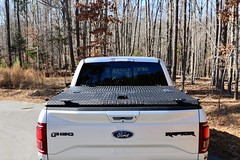 A Heavy Duty Truck Bed Cover On A Ford F150 Raptor (DiamondBack Truck Covers) Tags: aluminum tonneaucover truckbedcover diamondback diamondplate pickuptruck lightgrayorsilvertruck ford f150 raptor ff15 c ruggedblack hd heavydutytruckbedcover 0015000001fxaxyaah noaccessories outdoors woods closed rearview