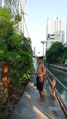 Fisherboy with fish along a Bangkok canal (ashabot) Tags: bangkok thailand citystreets peopleoftheworld people walk walkabout travel seetheworld seeasia adventure nomad wanderlust wandering globetrekkers boy fishing catch outdoor walking