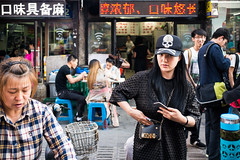 Memento mori. (spatialrhetorics) Tags: china street urban woman color colour hat skull eyecontact asia fuji candid streetphotography rangefinder mementomori fujifilm streetphoto streetfood changchun skullandcrossbones jilin dongbei colourstreetphotography valarmorghulis x100t fujifilmx100t
