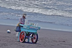 Snow cone vendor on the beach (Pejasar) Tags: scowcones vendor beach waves sparkle sand pacific ocean water colldown hat sell cold hot