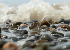Beached Wave (nikagnew) Tags: ocean beach wet water rocks bokeh stones wave bubbles
