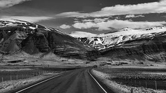 this would be worth a life on the road (lunaryuna) Tags: iceland southeasticeland onroutetohoefn landscape mountainrange sky clouds cloudscape ontheroadagain travel journey voyage roundtrip pastures fences snowcappedmountains geologicalformations weather lightmood spring season seasonalchange panoramicviews blackwhite bw monochrome lunaryuna