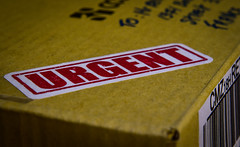 URGENT (Inspired by a song - Foreigner - 1981) (ericbeaume) Tags: macromondays inspiredbyasong macro nikon d5500 50mm 18g raynox closeup urgent writing letters cardboard cardboardbox barcode red ericbeaume