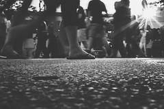 Herding (R*Wozniak) Tags: blackandwhite bw blackwhite crowd people 115 slowshutter a6000 streetlight sunburst legs sony pov dof sunlight lensflare 35mm