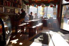 cafe light (KevinIrvineChi) Tags: chicagoist curbedchicago cafe louisiana sunny sunlight streaming inside indoors indoor customers people sony dscrx100 door cold benches wood wooden decorated decorations spoken particulates air bright books hardwood looking out eyes hand up reading coffee ravenswood montrose by train shadow shadows face profile