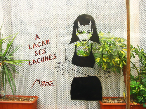 "graffiti from miss tic: a woman with devil horns, hands crossed in front of her, next to the words ""A Lacan Ses Lacunes"""