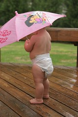 year 2, day 148 - the rain (-Angela) Tags: 2005 pink rain umbrella canon diaper 2550fav frombehind theson photoaday 2005top100faves