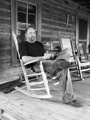 Mr. Johnson Rocks on Front Porch (Old Shoe Woman) Tags: usa georgia southgeorgia dilosep05 loghouse rockingchair man mrjohnson dilosept05bw dilosept05