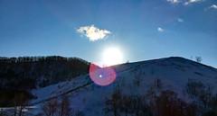 Coal Mine Tailings Sunset (sjrankin) Tags: 21january2017 edited yubari hokkaido japan sun sky clouds coaltailings tailings trees lensflare