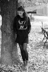 Memories of the autumn (PIXXELGAMES - Robert Krenker) Tags: newspaper news cafe kaffee vienna wien snapshot unknown candid portrait portret schwarzweiss blackandwhite blacknwhite bnw fujifilm fujinon filmsimulation lifestyle street streetstyle urban streetphotographer streetphotography biancoenero miniskirt girl longhair tights black nylons shoes makeup fashion shirt leaning tree leaves bokeh