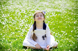 Happy cute little girl sitting on the daisy meadow and enjoying sunshine. Moment of happiness