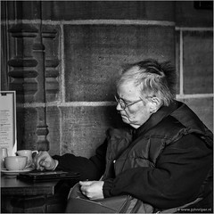 E-reading lady (John Riper) Tags: johnriper street photography straatfotografie square bw black white zwartwit mono monochrome candid john riper canon 6d 24105 l liverpool england uk ereader ereading lady woman terrace coffee menu church bag old body warmer cups glasses