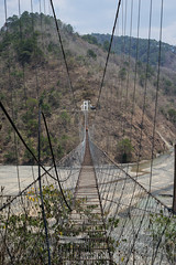 A man crosses a cable bridge above a river (Gus Cantavero Film & Images) Tags: travel bridge mountain vertical river asia outdoor sony voigtlander philippines hill cable symmetry baguio mountainside nokton distant foothill a7r