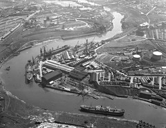 Shipyard of Sir James Laing & Sons, Sunderland (Tyne & Wear Archives & Museums) Tags: riverwear aerialphotography sunderland sirjameslaingsonsltd shipbuilding shipyards deptfordyard ships wearmouthcolliery wearside industrial industry reflection calm water land bank river aerialphotograph blackandwhitephotograph passage crossing digitalimage industrialheritage archives northeastofengland unitedkingdom wearmouthbridge bridge vessel piers pallion shipbuildingheritage maritimeheritage aerialtouroftheriverwear austinpickersgill jlthompsonsons sirjameslaingsons marineengineeringindustry engineworks williamdoxfordsons georgeclark glassmaking coalmining mining riversidecoalstaithes traditionalheavyindustries businesses economy infrastructure city urban crane interesting impressive fascinating unusual buildings container road rail transportation vehicle carpark grain blur landscape glimpse view deck cabin mast boat roof chimney