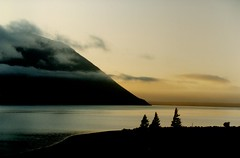 Lake Ohau at dawn (Brenda Anderson) Tags: newzealand sun mountain lake water silhouette clouds sunrise geotagged top20sunrisesunset calm serenity nz lakeohau ohau scannedprint curiouskiwi intop40set imagekind utatasilhouette geo:lat=44265609 geo:lon=169843483 brendaanderson utata:color=black utata:project=upfaves ourspacenz curiouskiwi:posted=2004