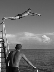 Launching into mid-air (Lil [Kristen Elsby]) Tags: blackandwhite bw lake beach water clouds pier frozen flying topf75 asia dive diving wharf editorial midair diver suspended itsongselection1 topv3333 centralasia kyrgyzstan socialdocumentary reportage lakeissykkul issykkul tienshan perfectingladolcevita itsong–canong5 documentaryphotography flickreditorial