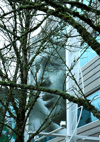 Bill Bowerman poster obscured by mossy trees outside Nike Corporate Headquarters, Beaverton, Oregon winter spring 2004-2005. Coach Bill Bowerman invented of waffle sole for running shoes and helped to spread the gospel of jogging by Wonderlane