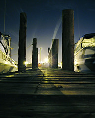 Dock lights (eqqman) Tags: longexposure light shadow newyork topf25 water silhouette night dark boats bay dock chaos topv1111 award 100v10f longisland flare mysterious bayshore incandescent topi pilon lightbeam