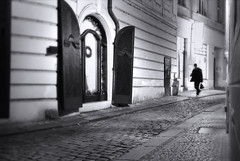 Prague Travels (Robert-Jan van Lotringen) Tags: prague praga city cobbles street streetphotography man traveller suitcase travel christmas night nightphotography black white noir bland bianco nero negro schwarz weiss czechrepublic europa olympus pov candid