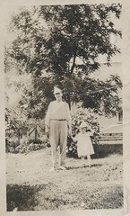 Father and daughter wearing paper hats (simpleinsomnia) Tags: old white black girl monochrome yard vintage found outside blackwhite holding hands little antique father snapshot daughter hats photograph littlegirl vernacular holdinghands foundphotograph