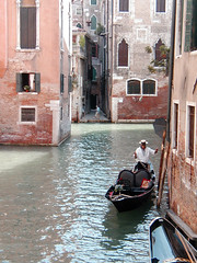 Gondelier (Jae at Wits End) Tags: city pink venice red urban italy building brick window water glass architecture outside boat canal italian alley europe exterior ditch outdoor structure backstreet alleyway lane shutters vehicle gondola venetian opening portal passage metropolitan waterway gondolier passageway