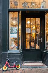 My Bike (Streetphotography by Joost Smulders) Tags: streetphotography straatfotografie candid urban city stad utrecht holland nederland zadelstraat fiets kinderfiets bike child kinderen people mensen winkel shop kleur color colour licht light olympus om24mmf20 feestelijk feestdagen
