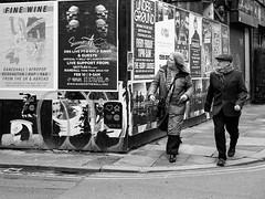 Northern Quarter #165 (Peter.Bartlett) Tags: manchester niksilverefex woman walking unitedkingdom urbanarte people noiretblanc corner olympuspenf hat streetphotography poster city peterbartlett lunaphoto man urban flatcap candid uk m43 couple monochrome bw microfourthirds sign blackandwhite facade fence