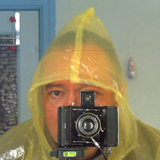 reflected self-portrait with Zeiss Nettar 515 camera and emergency poncho (square crop)
