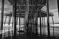 Kaliwo (eCHstigma) Tags: ocean california blackandwhite reflection building beach water monochrome architecture zeiss coast pier sand nikon waves pacific structure mysterious d750 serene centralcoast pismobeach bnw soothing distagont225 distagont225zf2