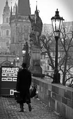Man with hat (paan.C) Tags: prague man coat charles bridge panc czech nikon d3300 hat statue lamp light building bwemotions seebw bag paint street history bnw black white noiretblanc