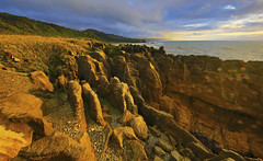 Pancake Rocks : Punakaiki (Clement Tang **bbbusy**) Tags: travel newzealand summer evening eveningclouds sidelit hdr bluesky nature nationalgeographic concordians closetonature landscape northisland limestonestacks grandemaregroup seascape scenicsnotjustlandscapes rockformation lensglare worldtrekker