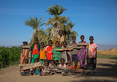Afar tribe children with wood boards in a coranic school with their teacher, Afar region, Afambo, Ethiopia (Eric Lafforgue) Tags: afambo afar africa calligraphy children colourpicture coran coranicschool danakil day education ethio17238 ethiopia fulllenght groupofpeople horizontal hornofafrica islam islamic koran kuran learning lookingatcamera madrasah madrassa madrassah muslims nomad outdoors palmtrees pastoralists pupil quran realpeople religion religious school students teacher tribal tribe woodboard worship afarregion et