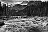 Rapids of the Mistaya River with a Mountain Backdrop (Black & White, Banff National Park) (thor_mark ) Tags: nikond800e day4 triptoalbertaandbritishcolumbia icefieldsparkway banffnationalpark lookingssw mountsarbach kaufmanpeaks mistayariver river blackwhite silverefexpro2 capturenx2edited colorefexpro outside nature landscape mostlycloudy overcast rockymountains canadianrockies mountains mountainsindistance mountainsoffindistance trees evergreens hillsideoftrees hillsideofrocksandboulders boulders largerocks mistayacanyon riverbank alongbanksofmistayariver snowcapped mountainvalley travelingicefieldsparkway travelingtheicefieldsparkway walktomistayacanyon centralmainranges waputikmountains northwaputikmountains christianpeak hanspeak mistayacanyonarea project365 portfolio canvas alberta canada