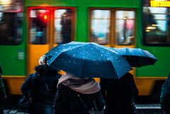 still motion (ewitsoe) Tags: street umbrellla standing tram passing ride rider commuter pedestrian womna parasol streetlight erikwitsoe poznan jezyce poland neighborhood city winter nikond80 35mm urban friday home bustle people