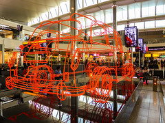 I Just Missed the Taxi (Steve Taylor (Photography)) Tags: heathrow art sculpture orange fun uk gb england greatbritain unitedkingdom london outline car auto automobile vehicle airport benedictradcliffe taxi terminal2 wireframe