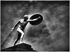The Gladiator (kurtwolf303) Tags: monochrome statue gladiator bw sw canoneos600d rays strahlen digitalphotography clouds wolken sky himmel dark dramatic unlimitedphotos topf25 250v10f interesting beautiful einfarbig outdoor fotorahmen frame 500v20f topf50 topf75 kurtwolf303 figur skulptur topf100 dramatisch 1000v40f topf150 1500v60f